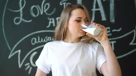 contato com os olhos : Cute young woman taking a sip of a glass of milk and making eye contact Vídeos