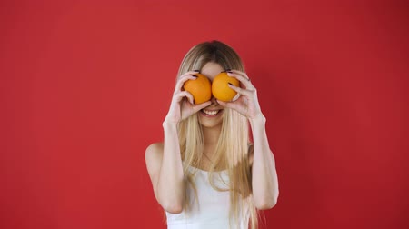 binocular : Portrait of amusing comic entertaining humorous laughable beautiful lovely cute pretty joke girl fooling around playing with orange slices, isolated on pink background. Stock Footage