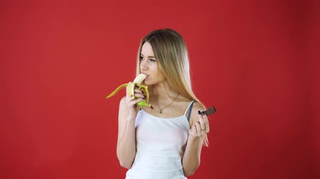 nervosa : Look woman with chocolate and banana trying to make a healthy choice to control her body weight isolated on red wall background. The expression of a human face