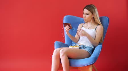 plodnost : The girl sits in a chair, watching a movie on the phone and eating popcorn