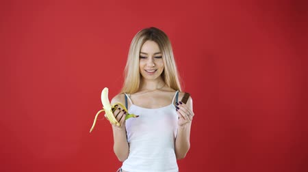 obżarstwo : Look woman with chocolate and banana trying to make a healthy choice to control her body weight isolated on red wall background. The expression of a human face