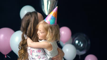 babygirl : The love of mother and daughter hugging and looking at camera. At the festival, mom and a little girl kissing Stock Footage