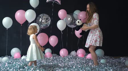 сестры : Portrait of a young mother and daughter having fun and posing with colorful helium balloons