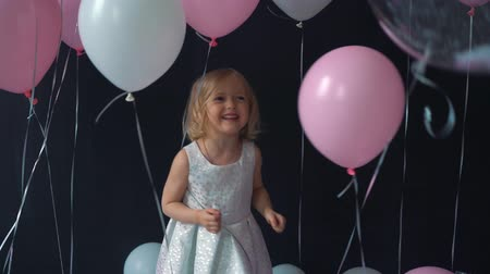 arejado : A portrait of a beautiful little girl smiles and holds in a hands color balloon in the studio with many balloons and a toy candy shop.