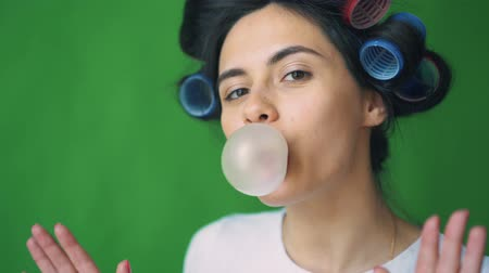 goma : Girl with curlers on her head and chewing gum, blowing bubbles on a green background, chromakey.