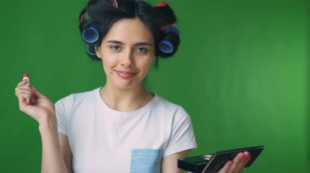 tusz do rzęs : Girl in curlers, doing her makeup. Green background, chromakey.