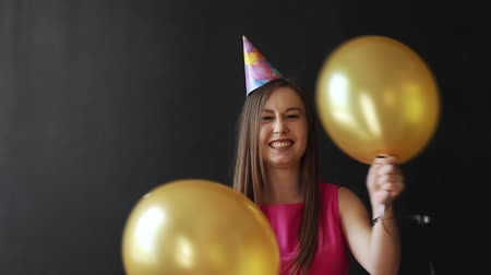 konfetti : Cute brunette holding Gold balloons on black background. Wideo