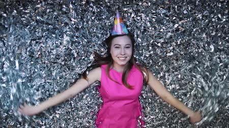 восхищенный : Happy young woman in pink dress celebrates New year or birthday on black background with confetti Стоковые видеозаписи