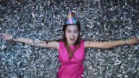 fete : Happy young woman in pink dress celebrates New year or birthday on black background with confetti Stock Footage
