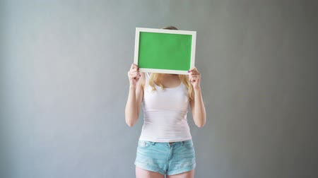 plakát : Attractive woman shows green key copy space with tracking points. The plate with a chromakey in the hands of the girl