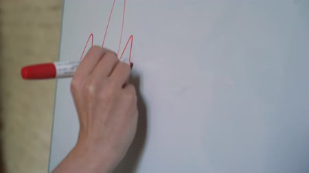 lower part : Businessman putting his ideas on white board during a presentation in conference room. Focus in hands with marker pen writing in flipchart. Close up of hand with marker and white board