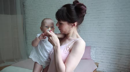 nipple : a child with a pacifier, mother holding her baby at the nipple