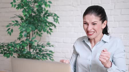 spam : angry young businesswoman shouting at her laptop