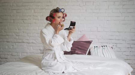 getting ready : A beautiful girl in curlers, in the morning after the bath paints her lips Stock Footage