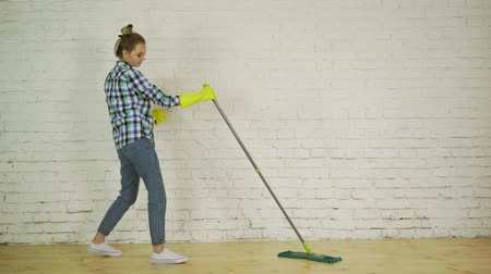 arrumado : Happy woman in sneakers to wash the floor to the music, dancing Stock Footage