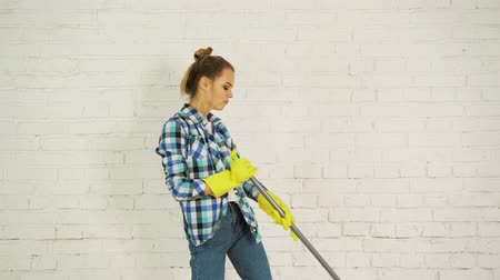 швабра : Beautiful young woman is dancing and smiling while cleaning floor at home using a mop