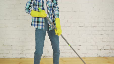 швабра : Cropped image of beautiful young woman in protective gloves using a flat wet-mop while cleaning floor in the house Стоковые видеозаписи