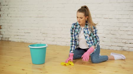 limpador : Shocked woman cleaning house with lots of tools. Young tired girl throws a rag in a bucket.