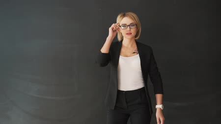popa : the business woman teacher with glasses and a suit. Put on and adjust the glasses before class