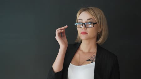 vidro : the business woman teacher with glasses and a suit. Put on and adjust the glasses before class