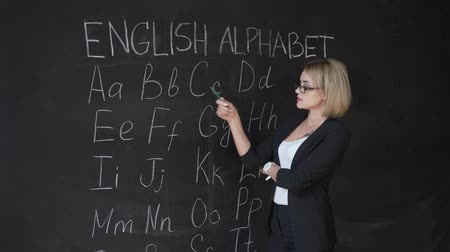 азбука : Teacher is writing letter of alphabet on blackboard with chalk. Education in elementary school concept. Стоковые видеозаписи