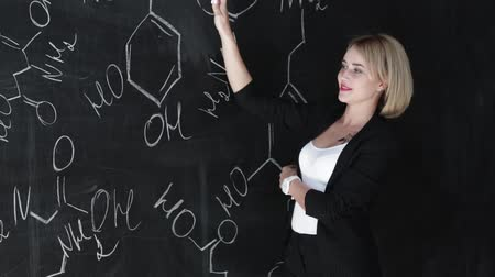 subject : Learn science or chemistry formula confident beautiful woman teacher chalk blackboard background
