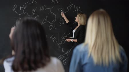 matemática : Teacher writing formulas on the chalk Board and explains the students the formula.