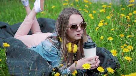 lefekvés : Beautiful young woman enjoys drinking coffee and lying on the grass.Woman drinking coffee.