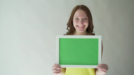 exibindo : Attractive woman with a chromakey sign in her hands, on a gray background. Stock Footage