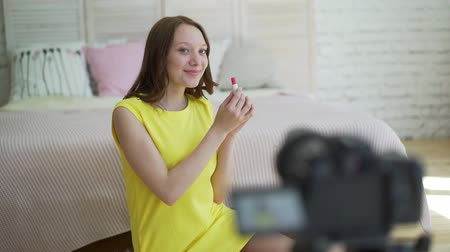 self promotion : Woman in yellow dress talking in front of camera to make a video blog.