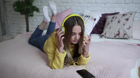 playlist : girl listening to music with headphones from phone at home. Stock Footage