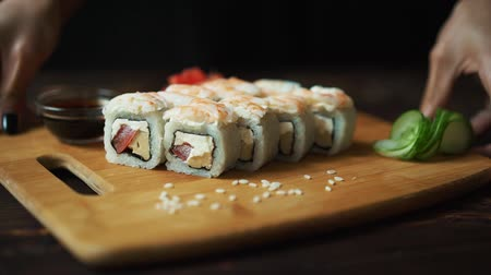 seafood dishes : Fresh sushi, rolls on the table. Dark background. Sushi sticks.