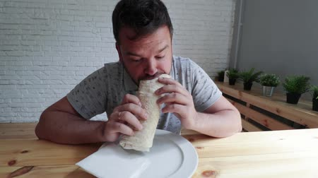 pita : Man eating Doner Kebap its a midlle eastern fast food cuisine