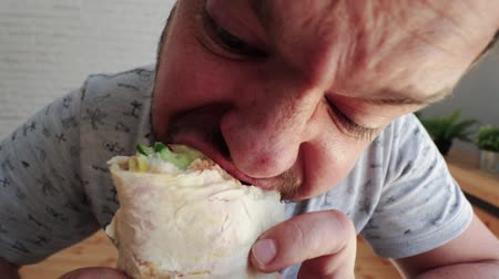 навынос : Man eating Doner Kebap its a midlle eastern fast food cuisine