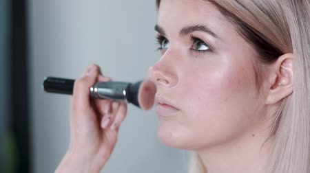 longhair : Make-up. Young Beautiful Girl making makeup with brush on cheeks. Stock Footage