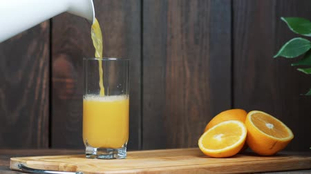 segmento : Freshly squeezed orange juice in a glass. Pour, squeeze orange juice. On a wooden background.