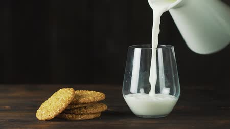 glass pitcher : Milk is poured into a glass at a slow pace, ideal for a diet for a healthy diet and can be used as a medicine. concept: diet, fitness, carbohydrates.