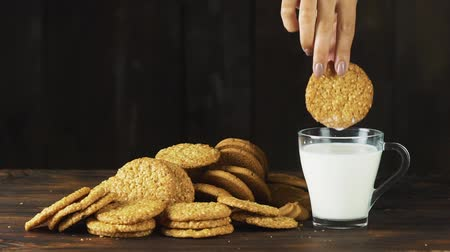 aveia : Hand putting a cookie in a glass of milk in slow motion. Food cinematic scene