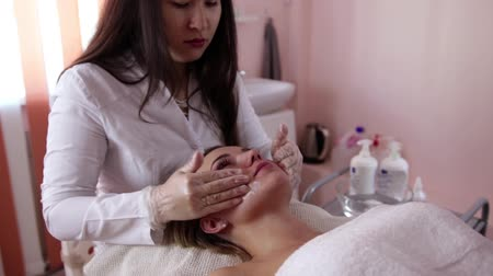массаж : Woman getting rf lifting in her face in clinic. Anti-aging RF-therapy, rejuvenation and lifting procedure.