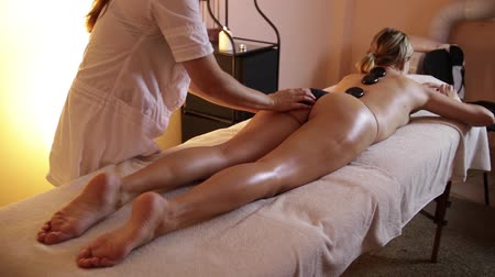 massagista : Beautiful Young Woman Receiving Hot Stones Massage At Day Spa. Multiethnic woman relaxing at spa center with a lastone therapy. Girl with eyes closed lying on massage table at salon