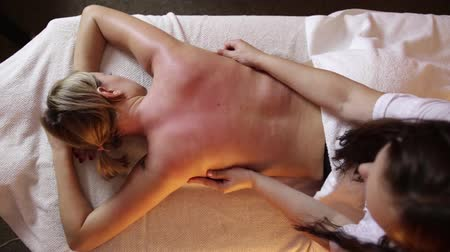 terapeuta : Beautiful young woman getting back massage in spa. Stock Footage
