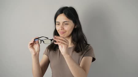 grey eyes : girl with glasses isolated on grey wall background. Stock Footage