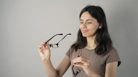 optyk : Young woman checking her new glasses in mirror on grey background. Young woman with glasses on grey background. Beautiful girl with glasses.