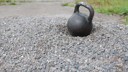powerlifter : heavy iron kettlebell competition in the yard-outdoor fitness concept. Kettlebell falls into a pile of rocks