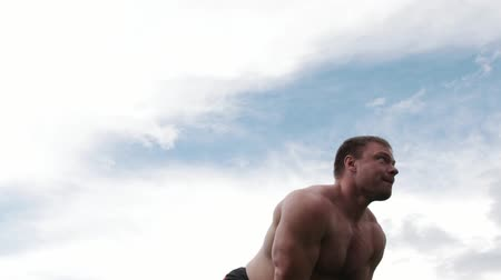 powerlifter : A strong man, crossfit, taking the kettlebells with both hands and tossing it in slow motion