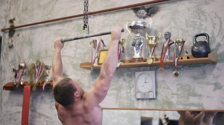 lift ups : Tilt up of shirtless sportsman doing pull-ups on bars during cross-training workout at gym Stock Footage