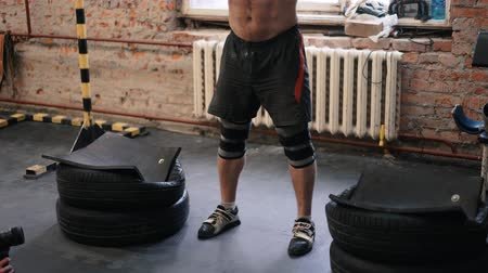 powerlifter : Athlete going to beat barbell snatch record at the gym with supporting team in slow motion.
