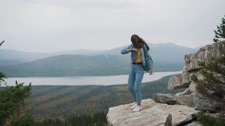 rejoices : Woman tourist on top is happy and celebrating success. A woman in a denim jacket on top of the world rejoices in a victorious gesture Stock Footage