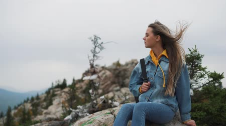 вершина : Attractive woman standing on a mountain peak with her long hair blowing in the wind smiling and trying to keep her hair off her face with her hand Стоковые видеозаписи