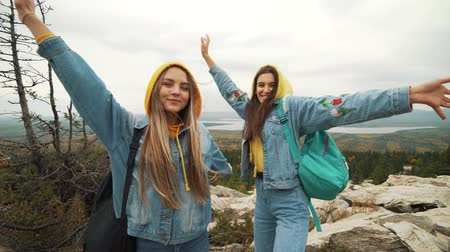 raised : Two young happy women dancing and raising arms on beautiful mountain top over sunset sky.